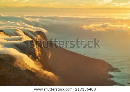 Cloud blanket and sunset at the top of the Table Mountain, Cape Town - stock photo