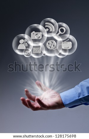 Cloud computing applications at your fingertips - male hand with media bubbles - stock photo