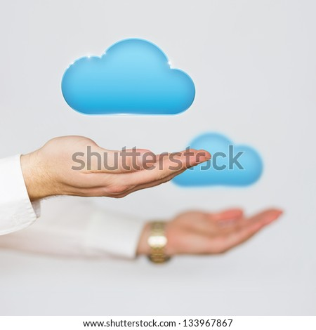 Cloud computing concept icons hovering over the hands of a businessman