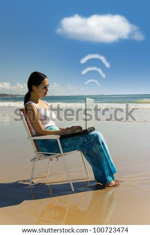 Cloud computing: woman with laptop working at the beach - stock photo