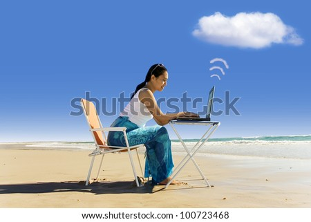 Cloud computing: working with laptop at beach - stock photo
