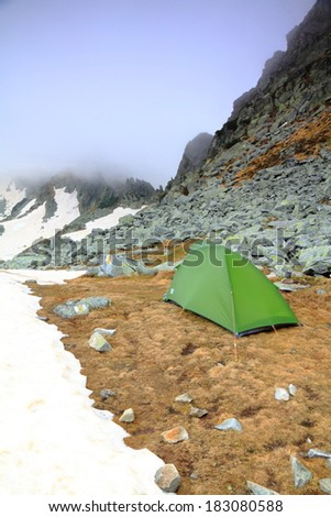 Cloud covered mountains and a green tent near the snow - stock photo