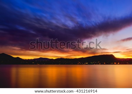 Cloud formation of a flying phoenix in the sky flying across Wanaka Lake towards the rising sun behind the mountain range