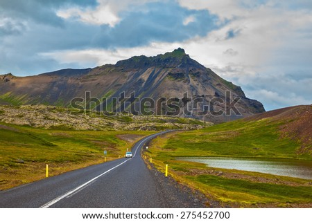 Cloud Iceland in the summer. The road passes through the picturesque landscape in the mountains and lakes - stock photo