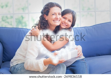 Cloud in shape of heart against happy mother and daughter hugging and smiling at camera - stock photo
