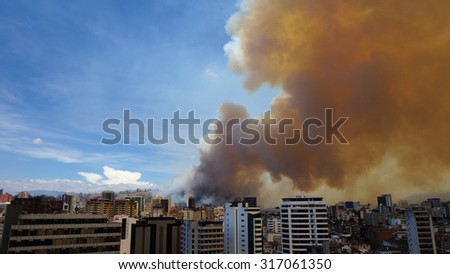 Cloud of smoke from forest fire near the city of Quito - Ecuador - stock photo