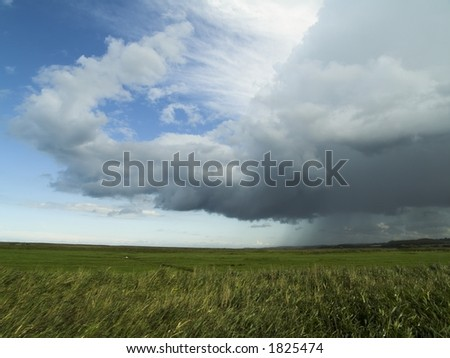 Cloud on the North Norfolk coast over Cley saltmarshes - stock photo
