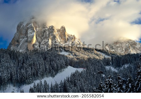 Cloud over the mountain. In the light of the sun. Ski resort of Selva di Val Gardena, Italy  - stock photo