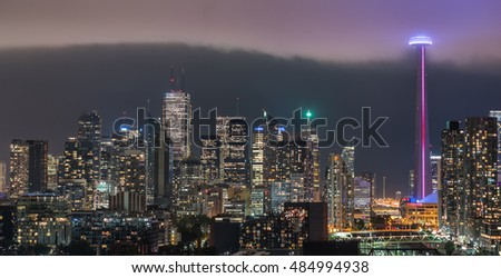 Cloud's edge cuts through hot humid night time air in Toronto, Canada.  Long exposure of urban illuminated skyline as rain cloud quickly moves in on a hot humid August evening. City glows with light.