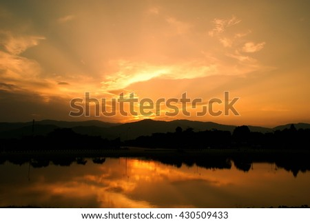 Cloud sky and sunbeam with lake and mountain background in sunset time