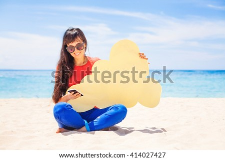 Cloud storage concept. Woman holding paper cloud icon on the beach