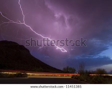 Cloud-to-cloud lightning over mountain peak with vehicle lights