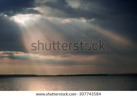 cloud water light beam. Beautiful sunset at the beach, amazing colors, View from the top of light beam over beach in summer - stock photo