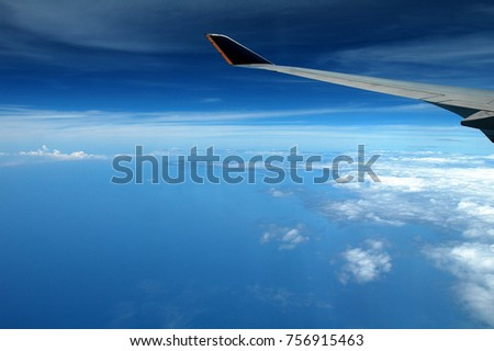 cloud & wing seen through window of aircraft