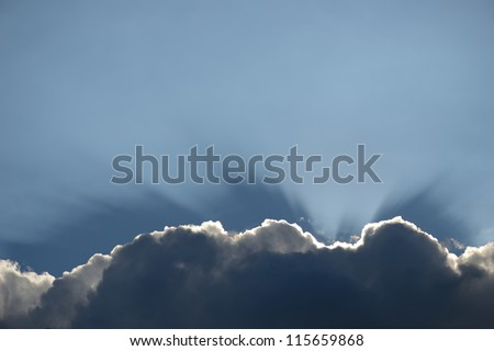 Cloud with a silver lining sun rays shining through that would make a nice boarder or footer to a page - stock photo