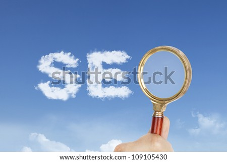 cloud with hand holding a magnifying glass spelling out  SEO