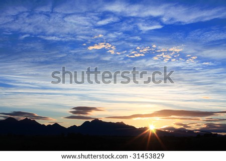 clouded blue sky with mountain silhouette - stock photo