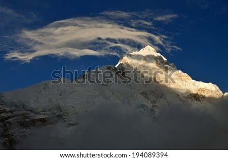 Clouds above Nuptse peak - stock photo