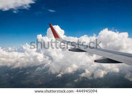 Clouds above the land as seen through window of an aircraft
