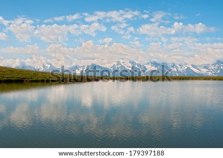 Clouds and blue sky reflect in the mountain lake. This is Caucasus Mountains - Georgia, Mestia region, Qoruldi lake.