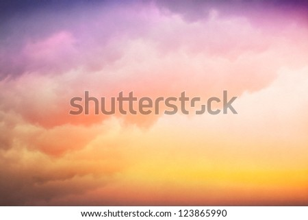 Clouds and fog with a colorful yellow to purple-blue gradient.  Image displays a pleasing paper texture visible at 100%. - stock photo