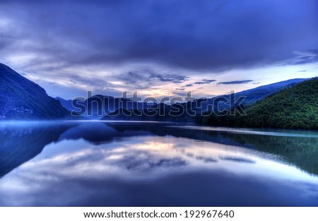 Clouds and mountains reflected in the lake - stock photo