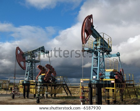 Clouds and pumps. West Siberia. - stock photo
