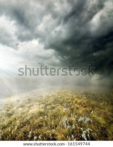Clouds and rain in the autumn field - stock photo