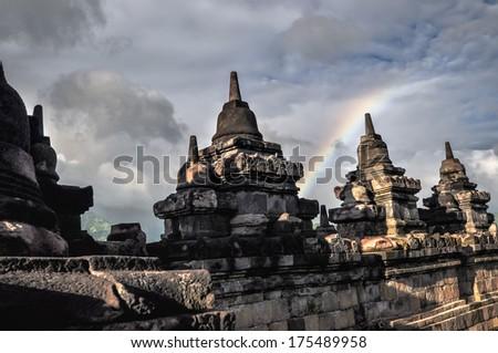 Clouds and Rainbow Buddist temple Borobudur complex in Yogjakarta in Java, indonesia - stock photo