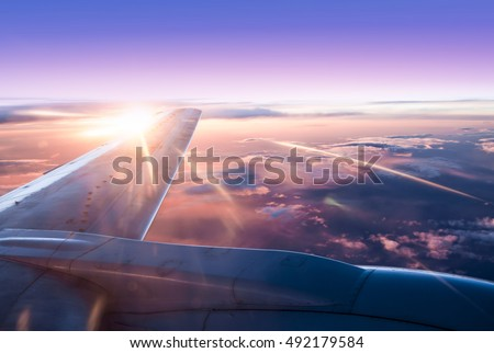 Clouds and sky and Airplane Wing as seen through window of an aircraft