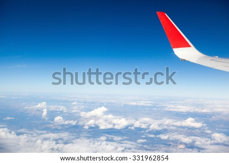 Clouds and sky as seen through window of an aircraft. Wing of the plane on sky background - stock photo