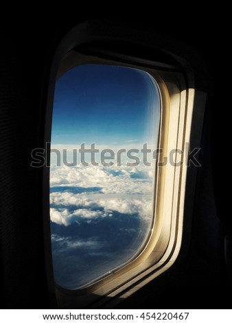 Clouds and sky as seen through window of an aircraft with retro color effect