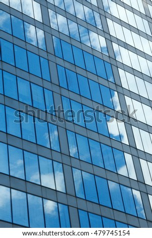 Clouds and sky reflection on a glass building facade.