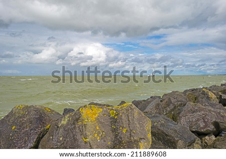 Clouds and storm over a dike in a lake - stock photo