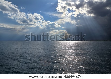 Clouds and sun rays over the sea. summer cloudy day on the lake.