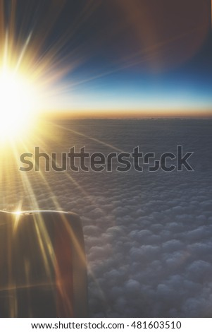 Clouds and sunlight as seen image through window an aircraft. Looking out the window of plane. Airplane in the blue sky at sunrise. View  wing from the inside on background sunset, mockup