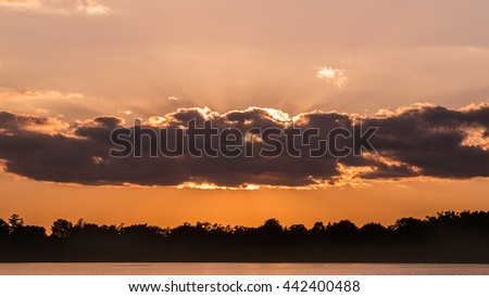 Clouds are flying over water during sunset time