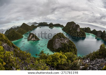 Clouds cover a gorgeous tropical lagoon in Wayag, Raja Ampat, Indonesia. This remote area is a maze of rugged limestone islands and coral reefs.  - stock photo