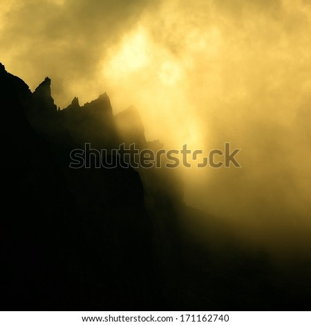 Clouds dramatically glowing over a mountain ridge - stock photo