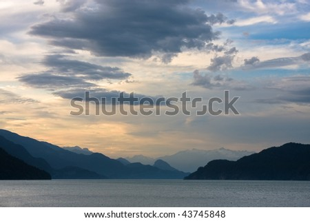 Clouds drift over Harrison lake (Canada) at sundown giving a desolate atmosphere - stock photo