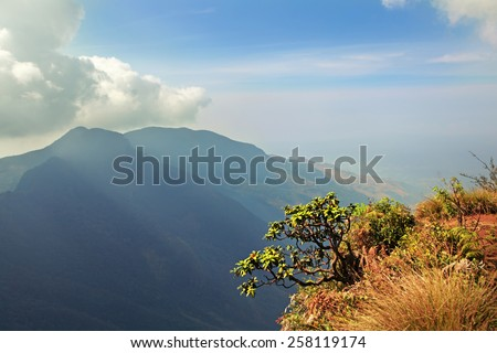 Clouds graze tops of the distant mountains - stock photo