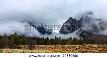 Clouds hang over jagged peaks of the Teton Range in western Wyoming - stock photo