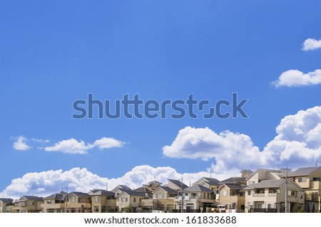 Clouds in blue sky over houses - stock photo