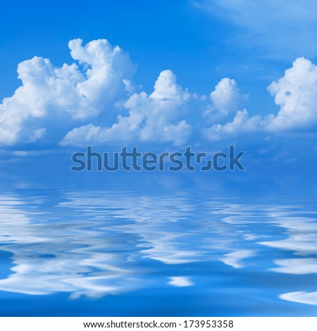 Clouds in the bright blue sky are reflected in a surface of water - stock photo