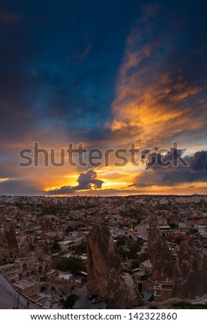 Clouds in the light of sunset over the town in mountains