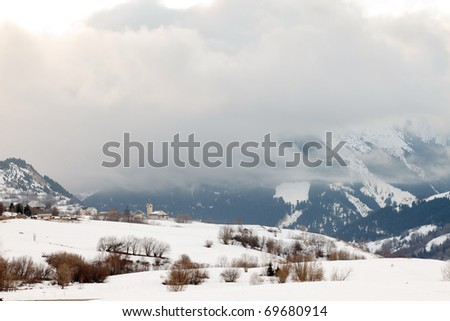 Clouds in valley with snow and little old church