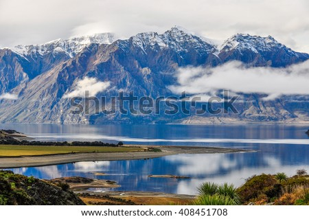 Clouds lying low over a lake near Wanaka in the Southern Lakes Region of New Zealand - stock photo