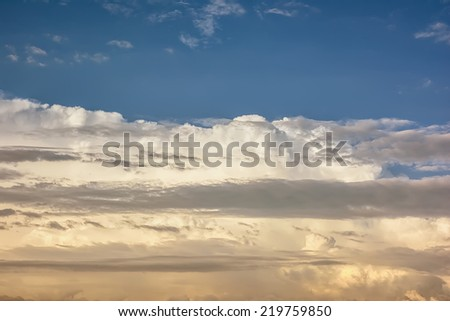 Clouds on a blue sky in the sunlight at sunset - stock photo