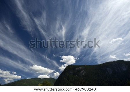 Clouds on the dark blue sky, with mountains