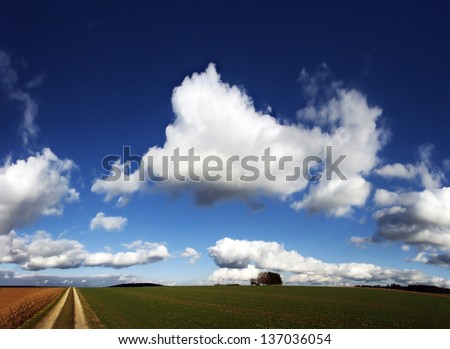 Clouds over a dirt road - stock photo